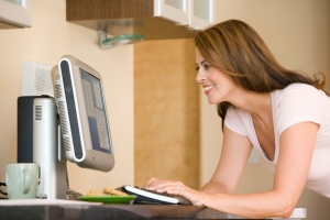 Woman in kitchen with computer smiling